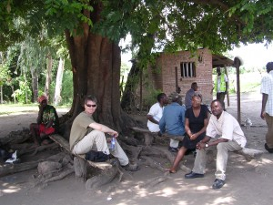 Jim, Loveness and Hassan wait under mango tree for go-ahead to install station