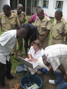Curious Malawian policemen watch Donna, Winstone and Patrick download seismic data.