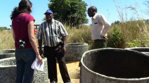 Myself and Watsan Facilitators, Mr. Mahugi (left) and Mr. Mbaga (right), at a shallow well construction point in Migungumalo. The well will be 6 to 7 meters deep and these cement rings will line the hole.