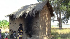 Myself infront of a tabocco house (bani) in Mbola Village, wood is fed into the house through the hole on the right which is connected to metal piping on the inside. Newer houses have clay piping and thicker roofs.