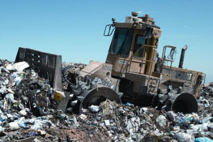 Bulldozer compacting solid waste at a landfill.