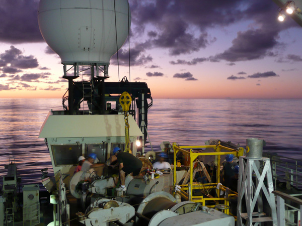 Crew from the R/V Atlantis work during the dawn hours to move a wire spool from one winch to another. The domed satellite dish that provides our Internet connection towers over the scene.