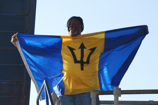 R/V Atlantis Wiper Leroy Walcott climbs out of the sub hoisting the flag of Barbados, which fittingly features a prominent trident symbol. Leroy is the first Barbadian to dive in Alvin. (Photo by Wanda Vargas)