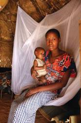 Mother and child in a Millennium Village with bed net to reduce malaria transmission