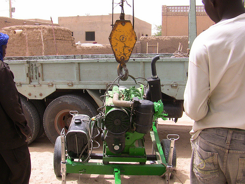 The two pump sets and accessories are loaded onto the truck by a crane and transported to the River Niger.