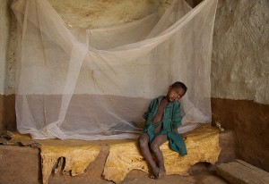 A boy sits by his brother, who is asleep under a bednet in the family household in Koraro, Ethiopia. Source: Millennium Promise.