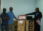 Ben Obera (second from left) helps unpack computers donated by Los Gatos High School to Kisumu Day School, its School2School partner.