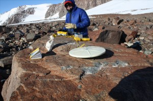Taking a sample from a huge boulder on a moraine that got left behind by a glacier
