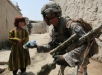 A U.S. Soldier hands an Afghan girl a bottle of water during an air assault mission, 2009. U.S. Army photo by Spc. Matthew Freire