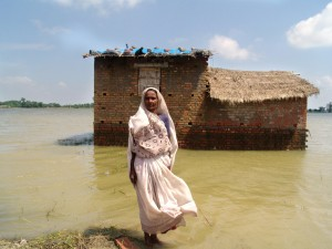 (c)CARE/Amelia Andrews Jinsi Devi in front of her mud house that is surrounded by water with the tarpaulin on the roof which she received from CARE as part of a relief kit.