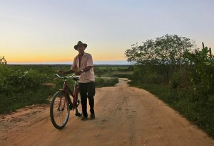 A man walks his bicycle at dusk along the road to Milhã, Brazil