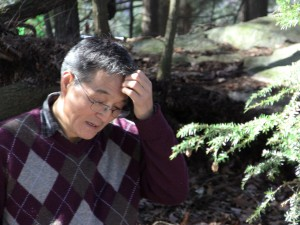 Seismologist Won-Young Kim considers his next step for the installation of a seismometer in the woods behind the Kent School's St. Joseph's Chapel.