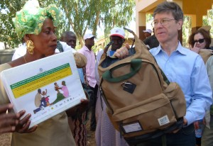 Jeffrey Sachs presents a backpack to community health worker Rokia, left, who works in the Tiby Millennium Village in Mali. Photo: Millennium Promise