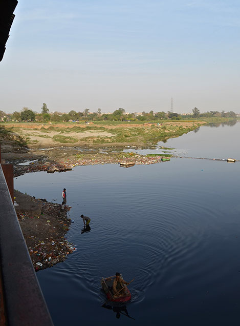 <h4>Boys search for change or other items of value in the brackish waters of the Yamuna river</h4>Delhi receives the bulk of its water from the Yamuna before it enters the city limits. But as it flows south through Delhi the river quickly becomes heavily polluted with industrial waste and untreated sewage. Nonetheless, the Yamuna is a sacred river for Hindus, and some court good luck by throwing coins into the water from the old railway bridge that spans it, in whose shadow these boys work.