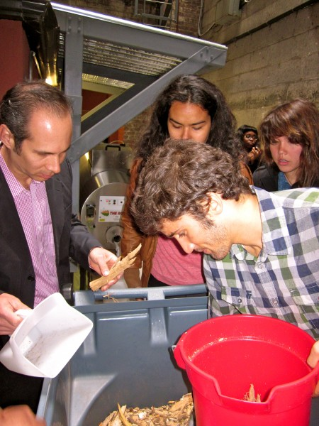 From left, Gerardo Soto from NATH Sustainable Solutions and students Aida Conroy and Adam Formica at the composter in Ruggles Hall. Photo: Melissa von Mayrhauser