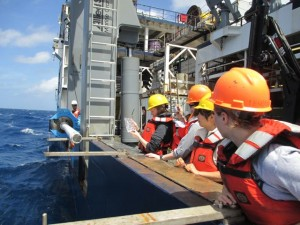 A sediment core is secured along the ship's rail for sampling.