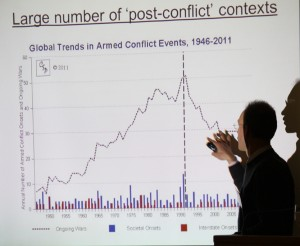 Man pointing to figure referring to graph of conflict trends