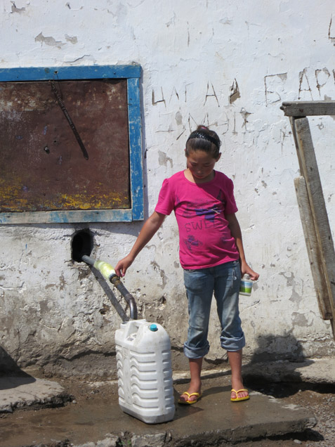 Surface water is not always dependable—or clean—so people in settlements rely on communal wells. This girl in the little town of Ugii Nur fills jugs for a small fee.