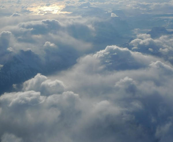 The west coast Greenland mountains tip through the clouds as the sun breaks along the ridgeline. (Photo M. Turrin)
