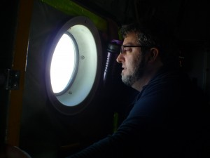 Chris Zappa,oceanographer and project optics expert, peers out the window of the LC130 aircraft.