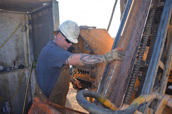 Driller Laurence Hill adjusts a pipe in the middle of his 12-hour shift. With a bit that whirls at 1,000 revolutions per minute and tons of heavy equipment driving it, his is a highly specialized and sometimes dangerous job.