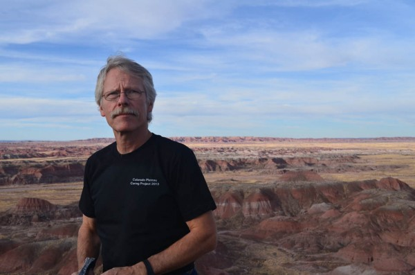 Paleontologist Paul Olsen of Lamont-Doherty Earth Observatory is co-leading a project in Arizona's Petrified Forest National Park to drill deep into rocks dating back more than 200 million years. Some sections lie exposed behind him in the badlands of the Painted Desert, which stretch beyond the park. The backdrop may look artificial, but it is real, and distances are deceptive. The ridge over Olsen's shoulders is about 8 miles away.