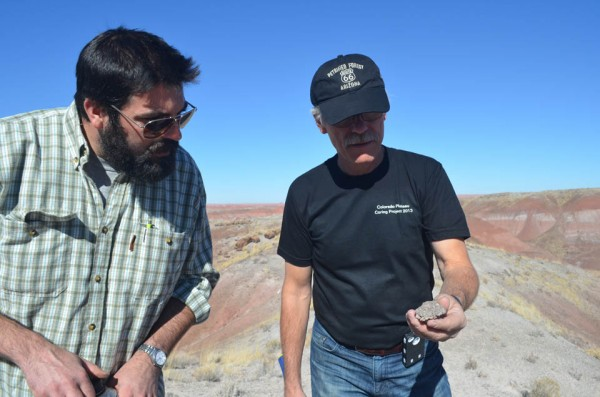 Schaller and Olsen discuss a rock found on the surface near the drill site. Even with all the technology at hand, old-fashioned shoe leather and a geologist's hammer are still indispensable for figuring things out.