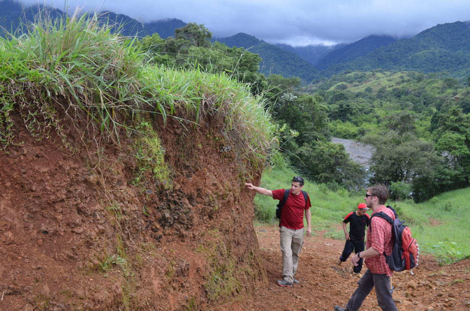 Much of the peninsula is a geologist's nightmare: covered with dense red soils and humid forests, there is hardly a rock in sight. Expedition leader Esteban Gazel of Virginia Tech (left) assesses terrain with a local volunteer (center) and Virginia Tech  grad student Jarek Trela.