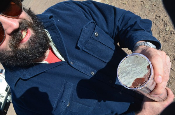 Geologist Morgan Schaller of Rutgers University shows off an unusual layer of greyish carbonate. Such layers may indicate sudden changes in the surface or the atmosphere, and give clues about climate shifts or other factors that affected living creatures.