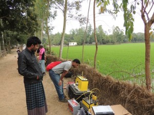 One of the Bangladeshi students checks the resistivity meter during the experiment while a local resident looks on.