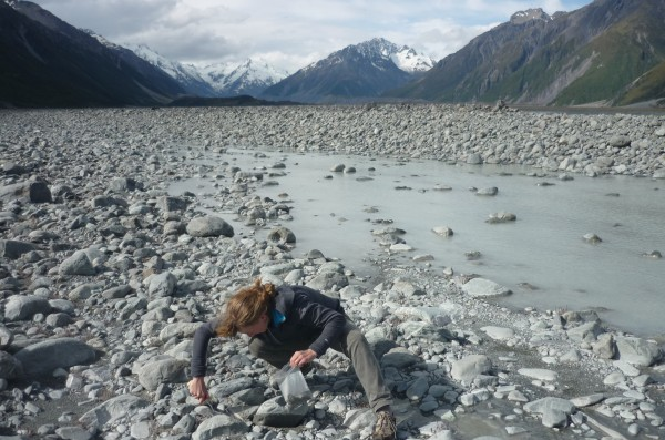 In January 2014, Bess Koffman traveled to New Zealand's South Island to collect some of this glacier-ground dust. In the stream bed above, she collects silt left by Tasman Glacier, which has retreated to its present location in the background, tens of kilometers up the valley since the last ice age. (Noah Pollock)