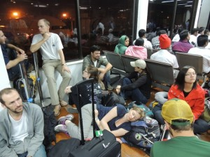 I very tired group of travelers waiting a Dhaka airport early in the morning.