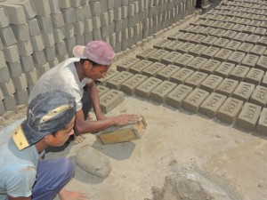 Tw of the workman shape the bricks using a mold.