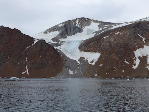 Magnus notes that the ice that drops down the red rock face of Kiatagssuaq remains year round. (Photo M. Turrin)