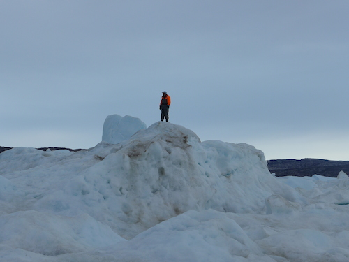 Gabriel Petersen climbs up to the top of the iceberg to check for open water. (Photo M. Turrin)