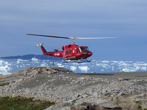 Landing at the Kullorsuaq 'helipad'. The helipad is surrounded by canisters of gasoline used to refuel for the return leg. The local transport of luggage and gear is a front loader that delivers the gear to your door. (Photo M. Turrin)