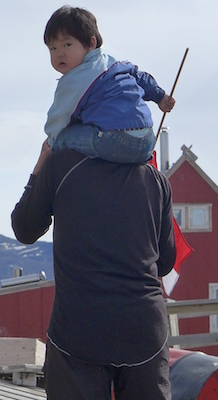 Community turns out to wait for helicopter.  Child is holding a Greenlandic flag. (Photo M. Turrin)