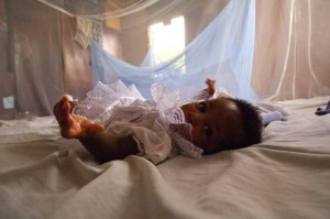 Infant in a malaria bed net. Photo: World Bank Photo collection