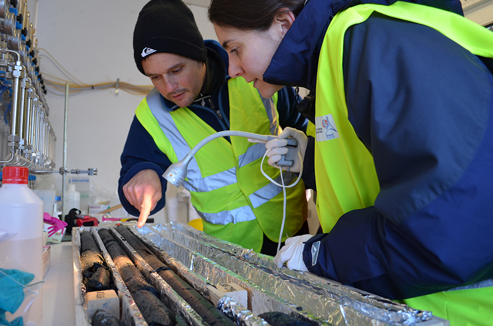 In a nearby shed, Lamont adjunct geochemist Juerg Matter (left) and microbiologist Rosalia Trias of the Paris Institute of Earth Physics inspect a freshly retrieved core. Visual inspection and analysis of the rocks' chemistry and microbiology should help the team better understand and refine the process.
