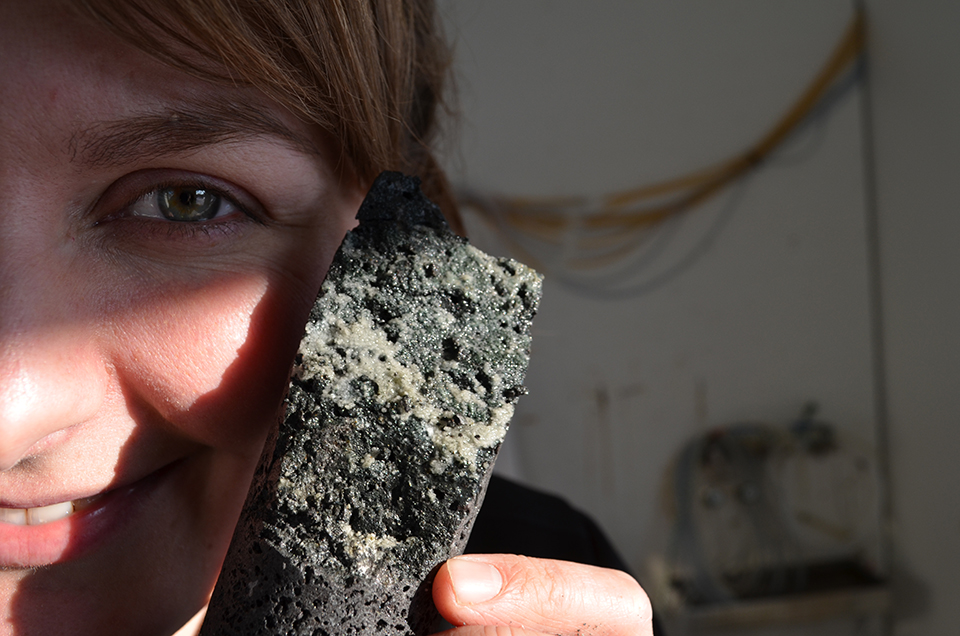 The prize of the day: University of Iceland geologist Sandra Snaebjornsdottir displays a core of porous basalt heavily laced with carbonate minerals—tangible evidence of the process at work.
