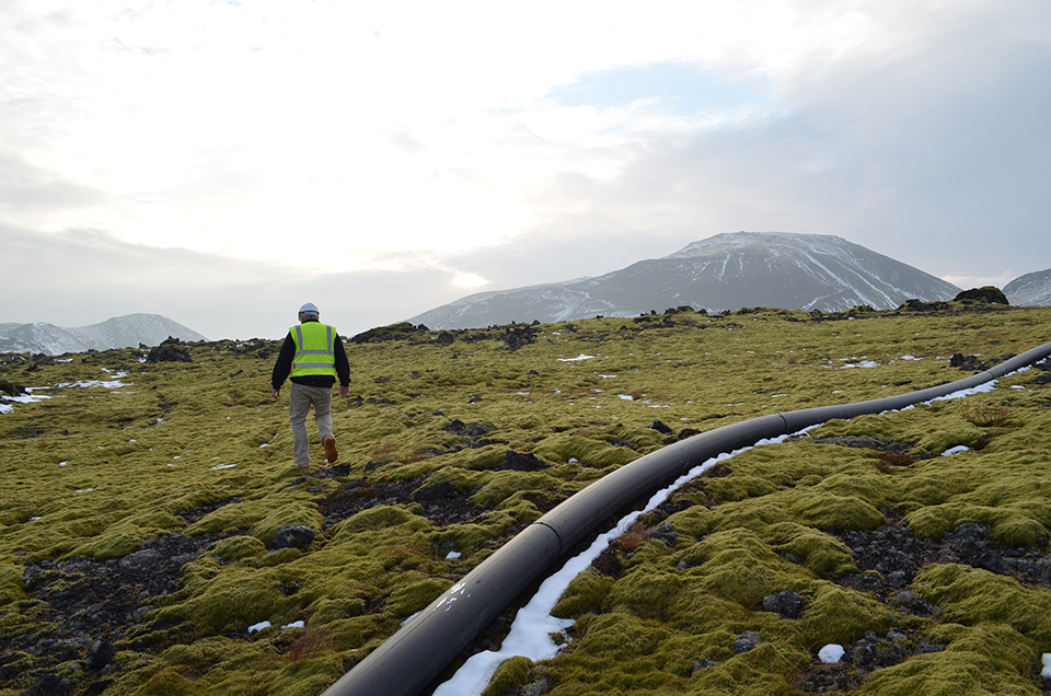 Over a plain of moss-covered basalt boulders, Lamont hydrologist Martin Stute passes a water-supply line near the Hellisheidi power plant. it is easy to think of Iceland's landscapes as set apart from the outside world—but they are intimately bound to it.