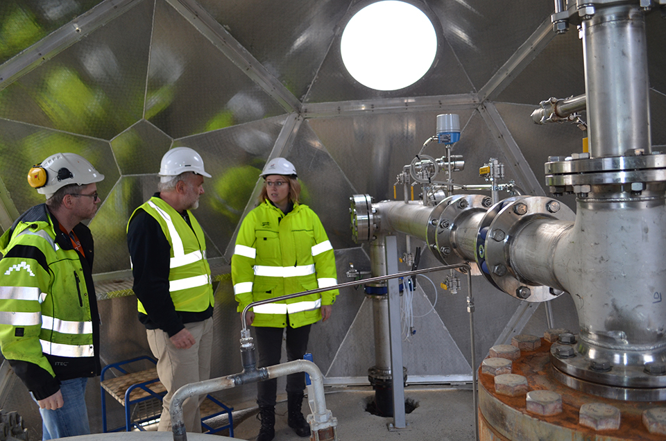 Inside, the injection pipe plunges 2,000 meters into the ground. CarbFix project manager Edda Sif Aradottir (right)  inspects the installation with Lamont-Doherty hydrologist Martin Stute and Arnarson.