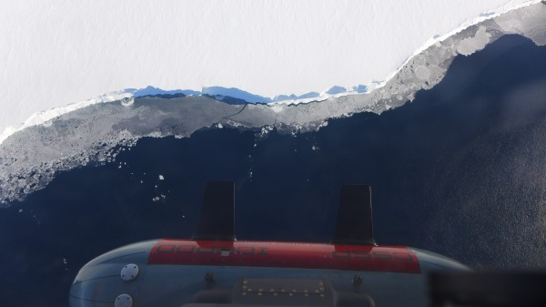 Icepod flying over the front of the Ross Ice Shelf. Along the shelf edge sections of thinner sea ice appear grey on the water surface. (Photo W. Chu)