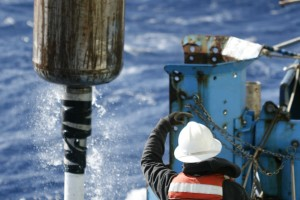 The ship's winch operator maneuvers the coring rig into place. A hollow steel tube is dropped over a previously targeted location and a lead weight propels the tube downward. (Gene Henry)