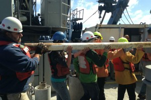 When a core comes up, it's all hands on deck. A plastic tube full of fresh sediments is pulled out of the coring device and hauled away for cataloging and analysis. (Charlie Langmuir)