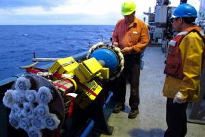 A third type of coring device extracts shattered volcanic rock from the sub-seafloor. The wax corer, as it's called, smashes into the basalt and catches the glassy debris on its wax wheels. Glass chips are extracted when the wax is later melted. Here, cruise leader Charlie Langmuir and Zhongxing Chen, both of Harvard, prepare the wax corer. (Yinqi Li)