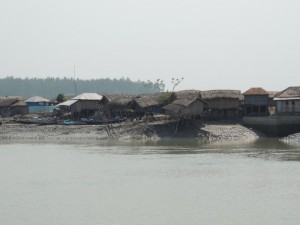 Homes on the edge of the eroding peninsula at Kalibogi