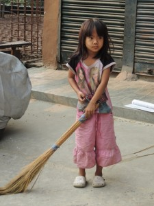 A little Mizo girl sweeping the street in front of her family's shop