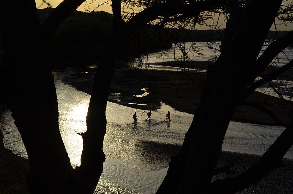 Northwest Kenya's Turkwel River runs through ancient lands where many key fossils and artifacts left by early humans have come to light. The region is now inhabited by the Turkana people. Near sunset, three boys frolic on their way to fetch water.