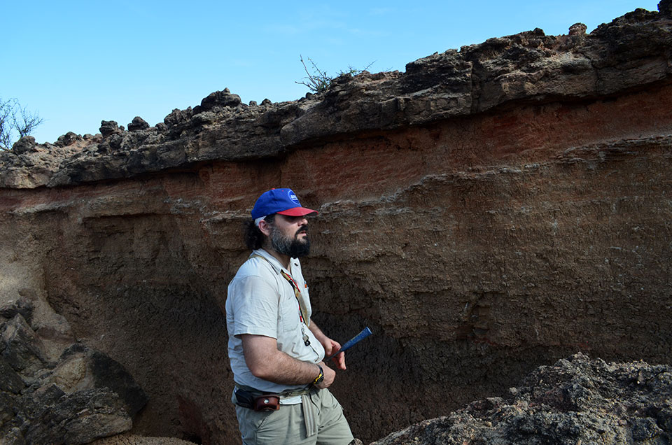Lepre prepares to sample an outcrop of ancient sediments. He establishes the ages of objects found within or near layers using magnetostratigraphy--the study of how earth's magnetic field periodically reverses itself. Changes in polarity can be identified by the orientation of mineral grains.
